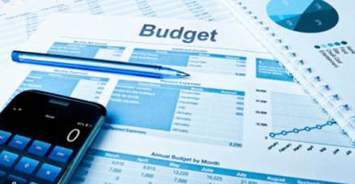 A calculator, pen, and other paper-based budget planning tools