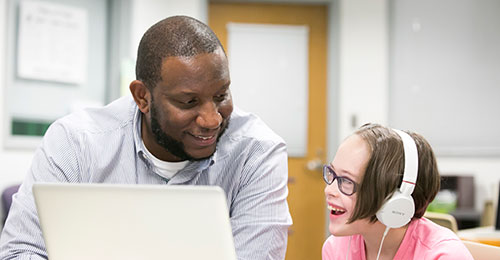A paraeducator working with a student at the computer.