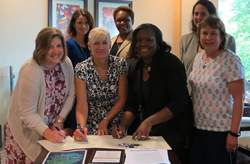 Staff from Alpha Phi Alpha Fraternity Inc., Kappa Phi Lambda Chapter and HCPSS signing partnership agreement