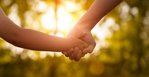 Two hands being held in front a shining sun.