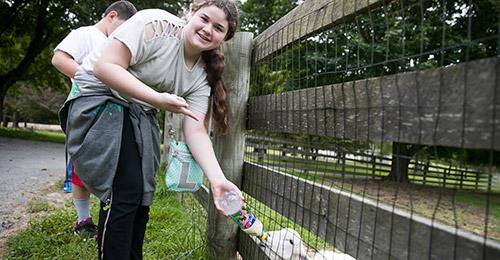 Student feeding a baby goat