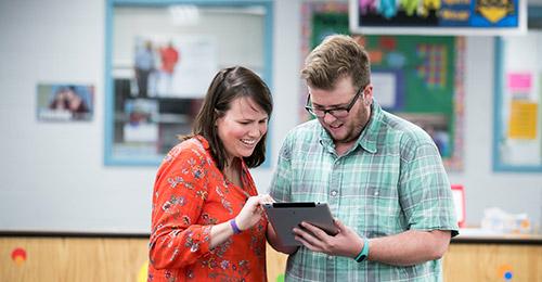 Lora Koehler helping colleague with iPad.
