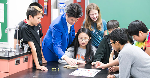 Sung Kim working with students in classroom