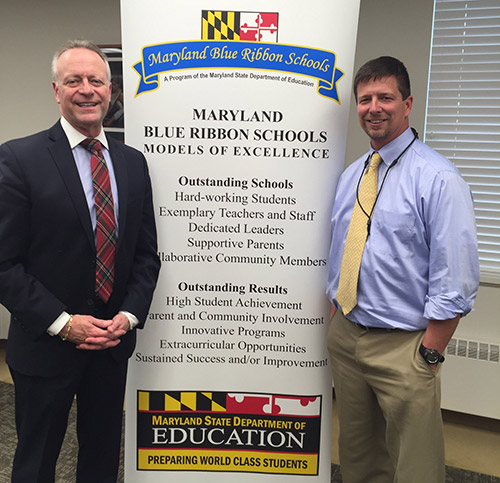 Dr. Martirano standing with Principal Sean Williams in front of banner. Main banner heading reads Maryland Blue Ribbon Schools Models of Excellence