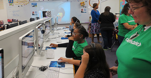 Female students in computer lab working on coding exercises.