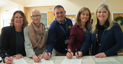 Group photo of school and partnership representatives signing agreement.