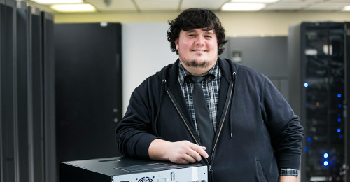 A proud Nick Vissari finishing a computer build in the server room