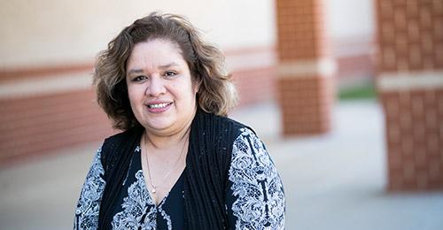Lori Miller standing in front of school.