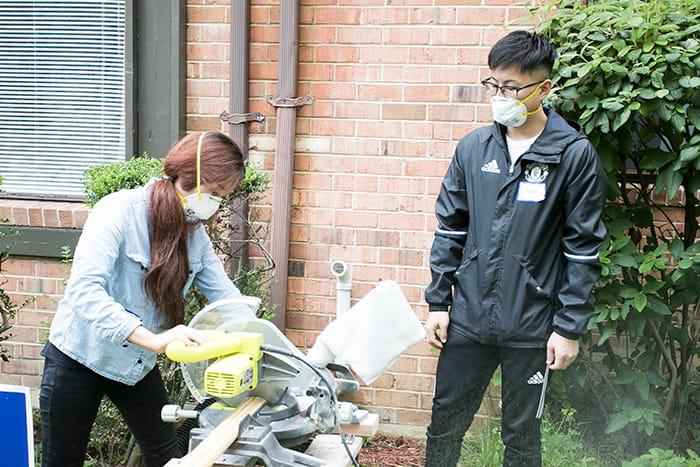OMHS students cutting trim with a circular saw.