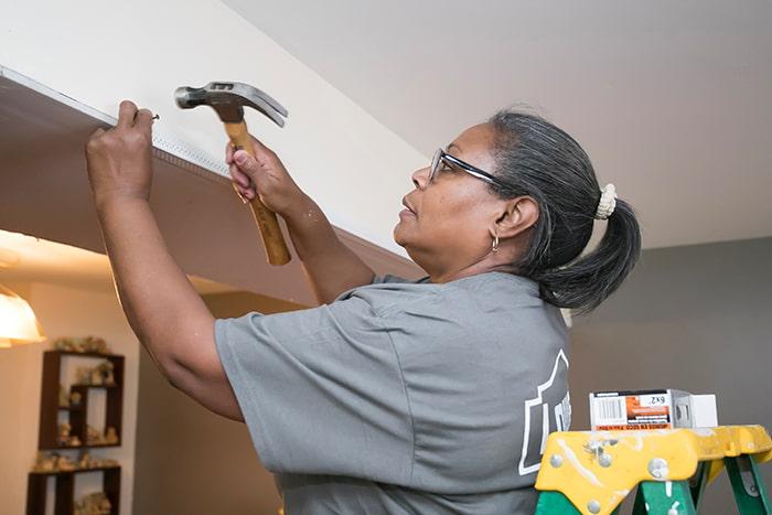 An OMHS staff member repairing a ceiling bulkhead.