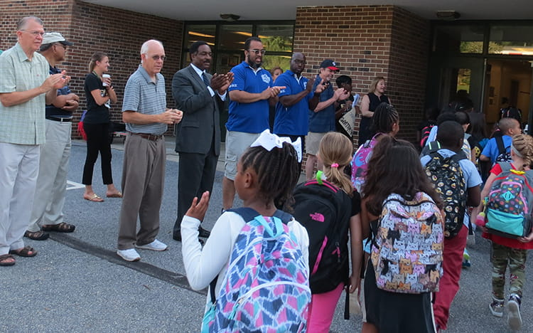 HCPSS partners clapping and celebrating BWES students as they enter the school building.