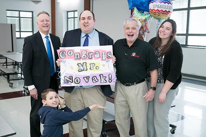 Principal Novak holding up a sign that says 'Congrats Mr. Novak!'