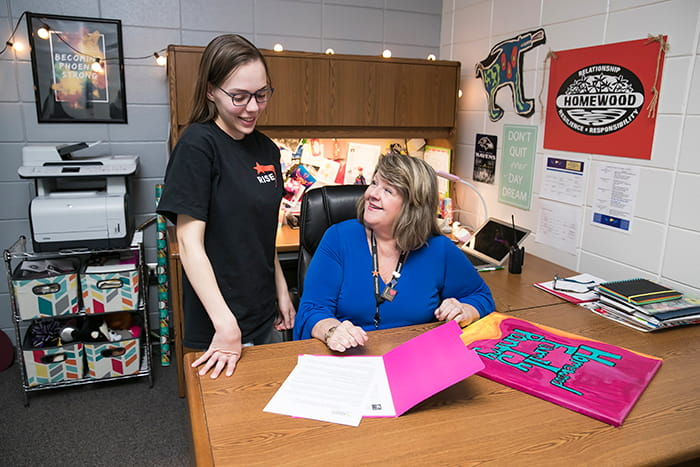 Suzanne McMurtray in her office working with a student.