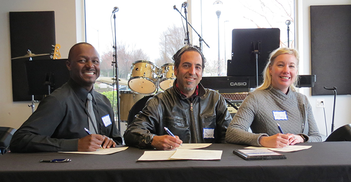 HCPSS Music Coordinator Terry Eberhardt, Triadelphia Ridge Elementary School Principal Tiffany Tresler and Bach to Rock Site Director Samir Moussa signing the partnership documents.