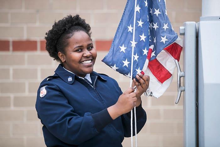 Female ROTC student is raising an American flag.