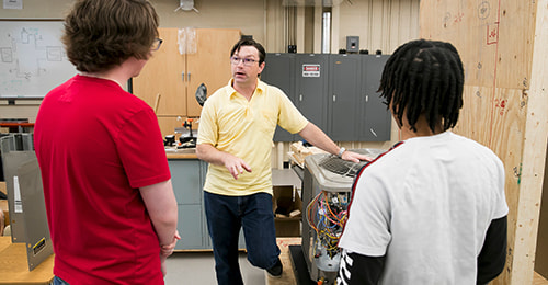 HVAC Academy Instructor Keith Artley discussing a HVAC system with students.