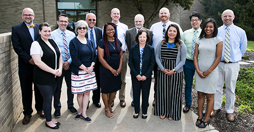 Senior class teachers of the year standing in front of the central office building.