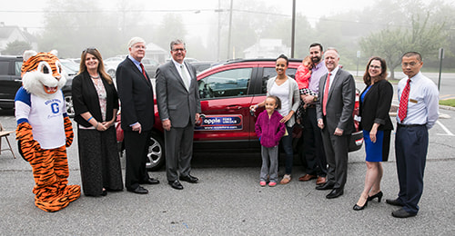 Superintendent Michael J. Martirano; members of the BOE; HCPSS Teacher of the Year Sylvia Hennessie and her family; and representatives from Apple Ford stand around Mrs. Hennessie's new vehicle.
