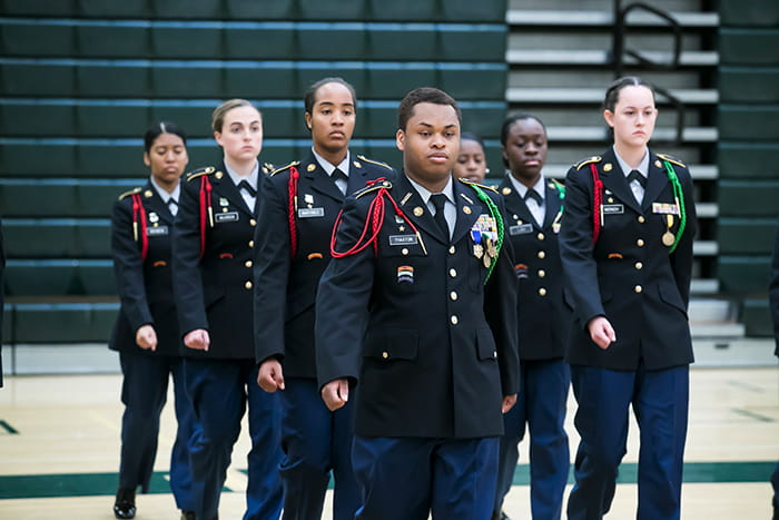 A group of ROTC students are walking in a formation.