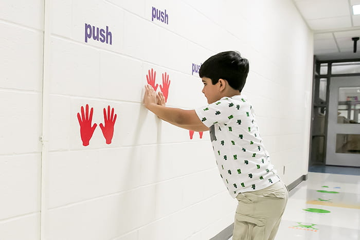 Male student putting his hands against a wall with handprints on it.