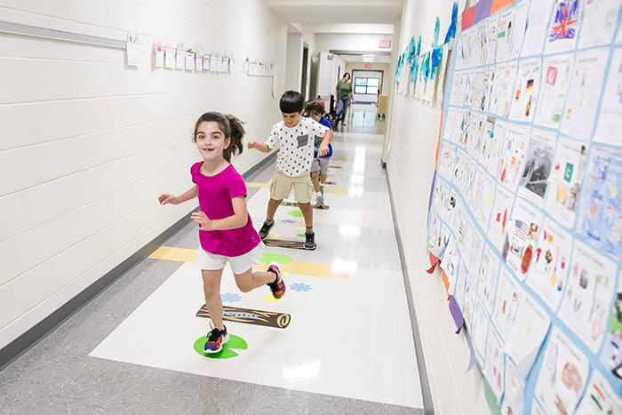 Young studets running through a hallway lined with artwork on the wall and designs on the floor.