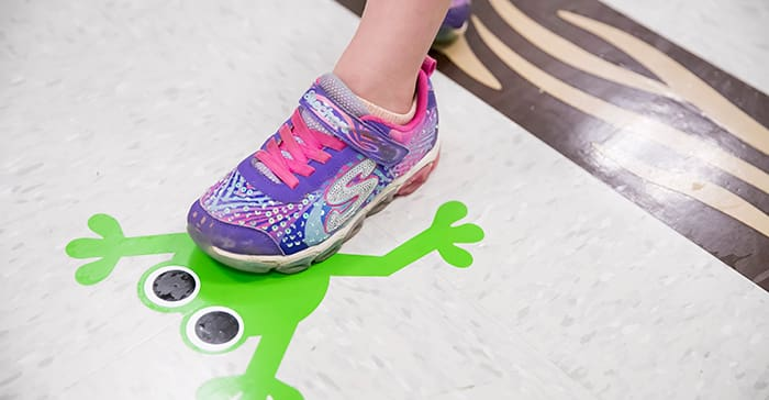 A young child's foot in a pink sneaker, standing on an image of a frog.