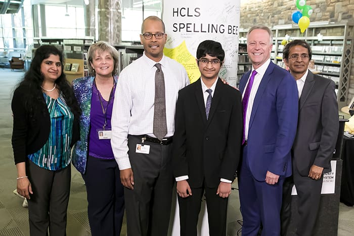 HCPSS Superintendent Matirano, Saketh Sundar, and a group of men and women stand in front of an HCLS Spelling Bee sign.
