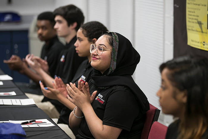 A female student seated at a table claps her hands alongside other seated students.