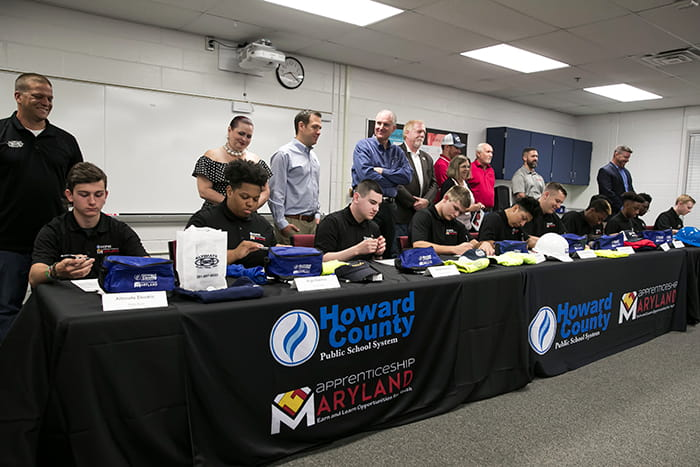 Students sit at a table and sign documents while a group of adults stands behind them.