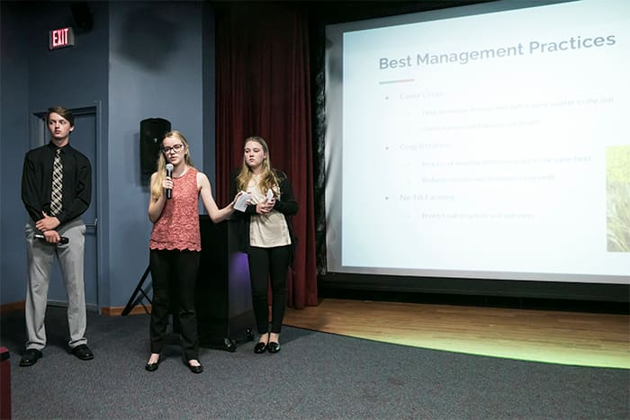 Three students deliver a PowerPoint presentation.