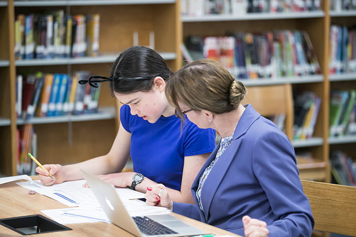 A female student and a teacher look over a document together.