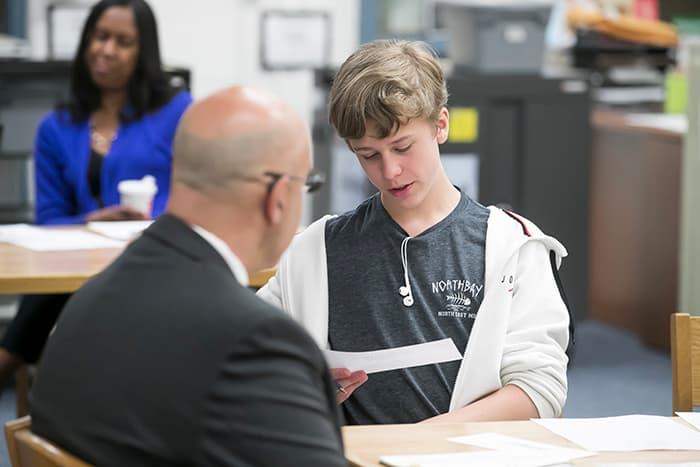 A young male student reads to a teacher.