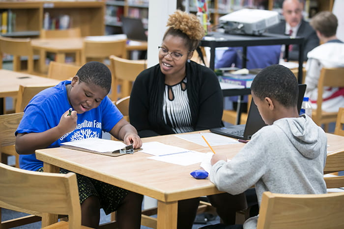 A teacher sits in a library with two students.