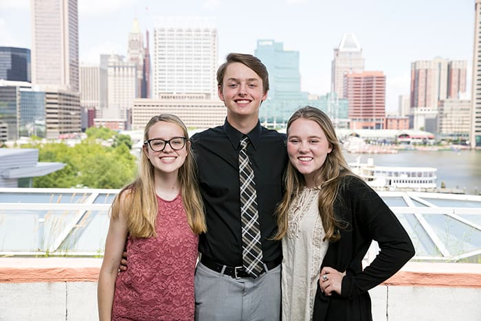 A male and two female students smile with the Baltimore skyline in the background.