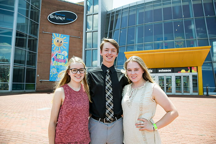 A male and two female students stand outside the Maryland Science Center.