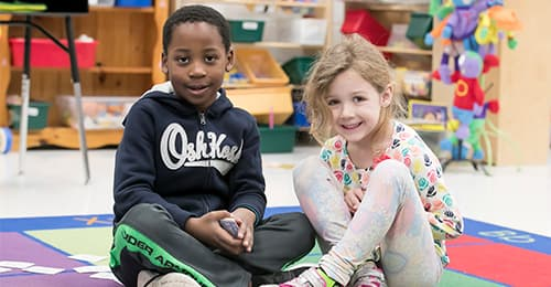 A young male and female student sit on a colorful mat in a classrom.