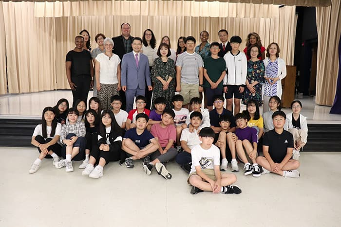 A group of students and representatives from South Korea's Iksan school district join HCPSS leaders on a stage.,