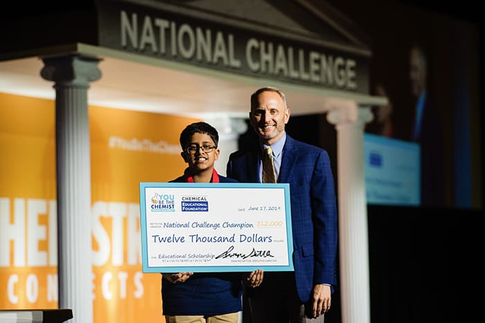 You Be the Chemist Challenge Winner Anurag Sodhi holds a check for $12,000.