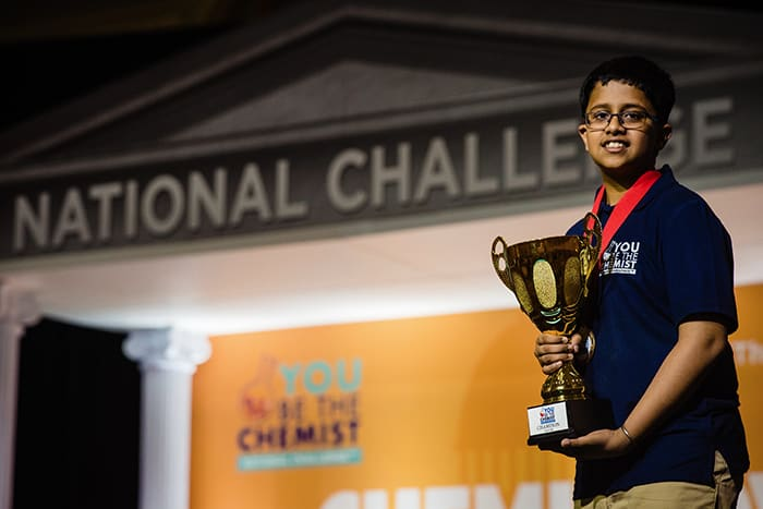 You Be the Chemist Challenge Winner Anurag Sodhi holds a trophy.