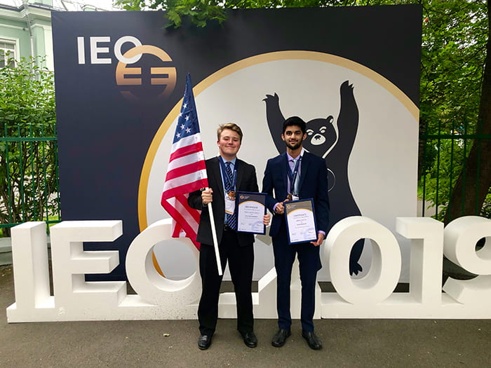 Aditya Krishna and Wyatt Currie hold their awards from the International Economics Olympiad (IEO).