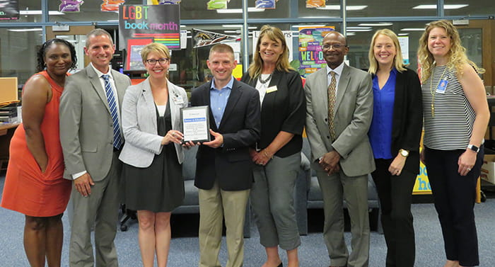 HCPSS staff and representatives from Comcast hold a plaque commemorating a new partnership.