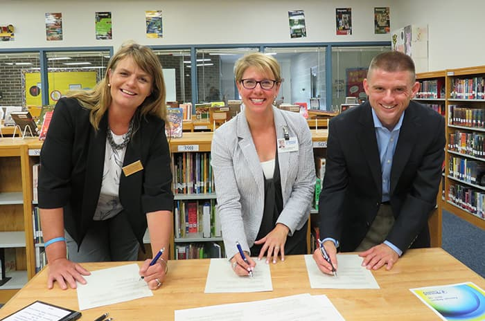 HCPSS and Comcast representatives sign a partnership agreement.