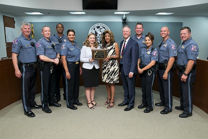 HCPSS Board Chair, Superintendent, and law enforcement officers hold a plaque.