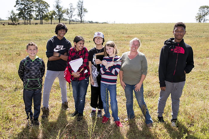 A group of Harper's Choice Middle School students in a field.