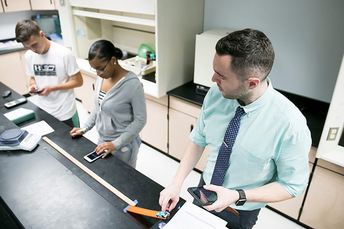 David Klotz in a lab with two students.
