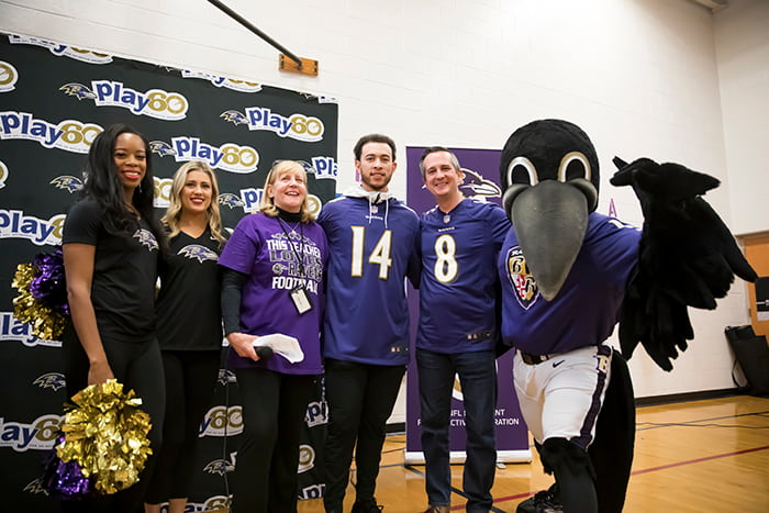 A Ravens player, cheerleaders, the Ravens mascot, and GES admininstrators.