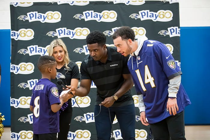 Two Ravens players and a Ravens cheerleader speak with a student.