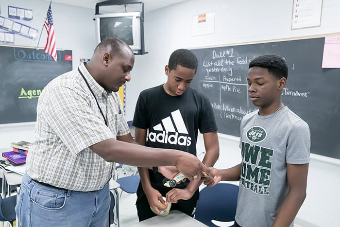 Two African-American PMS students and their teacher hold a model they are working on.