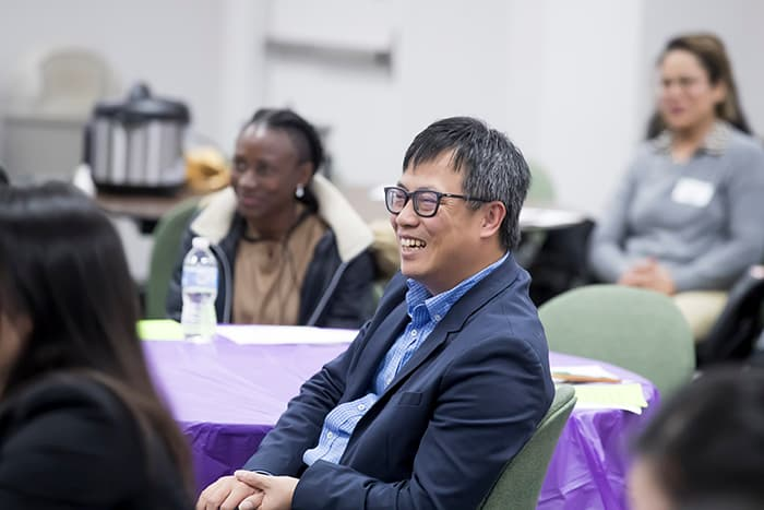 An Asian man smiling at an event.