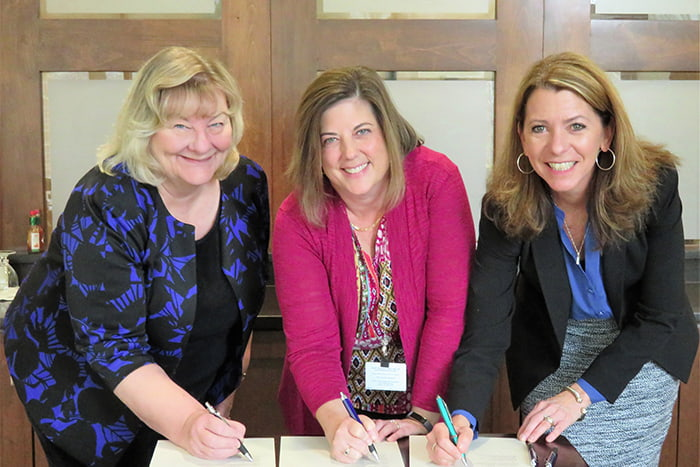 Three women signing a partnership agreement.